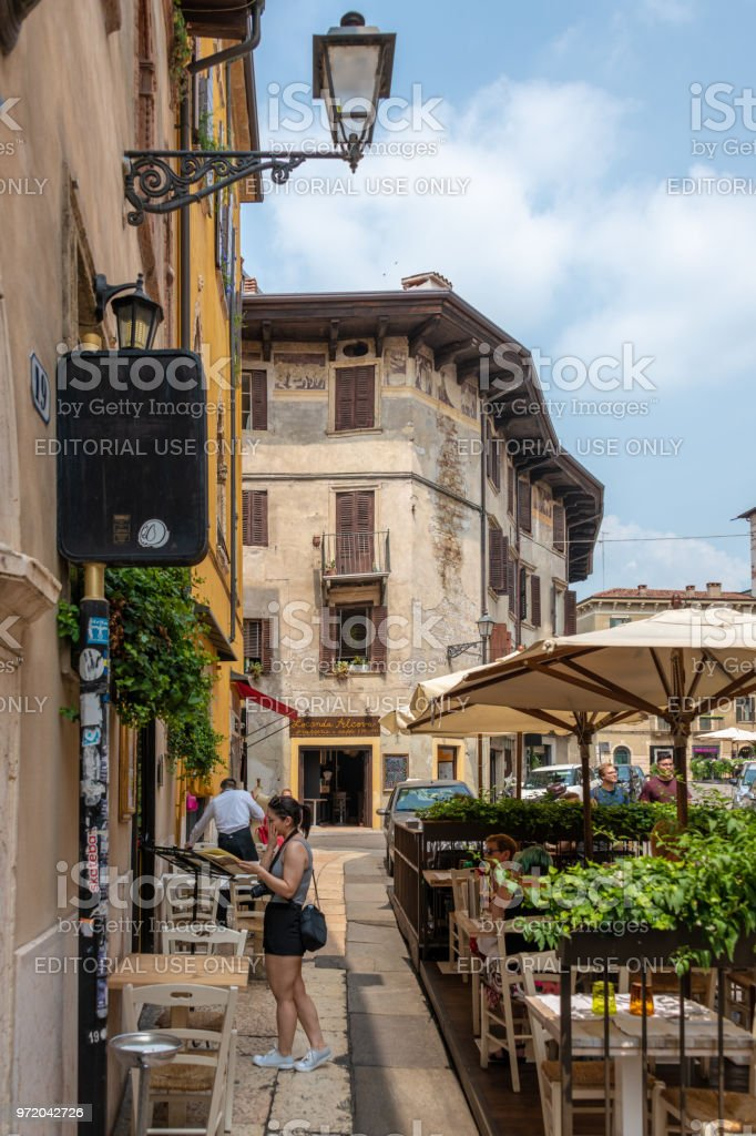 Young lady looks at a cafe's menu while on the phone in Verona, Italy stock photo