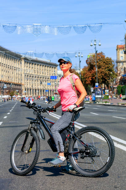 A young lady on a mountain electric bike stands on the road of Khreschatyk Street in Kyiv. Portrait of young lady in jeans and pink t-shirt while riding on electric bike along city streets of Kyiv, Khreschatyk, on a bright summer day. Bicycle trend in the city. electric bike and classic bike stock pictures, royalty-free photos & images