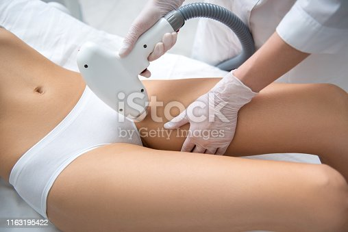 Aesthetic body treatment. Close up top angle portrait of cosmetologist making hair removal procedure of bikini zone to young relaxed woman in white underwear