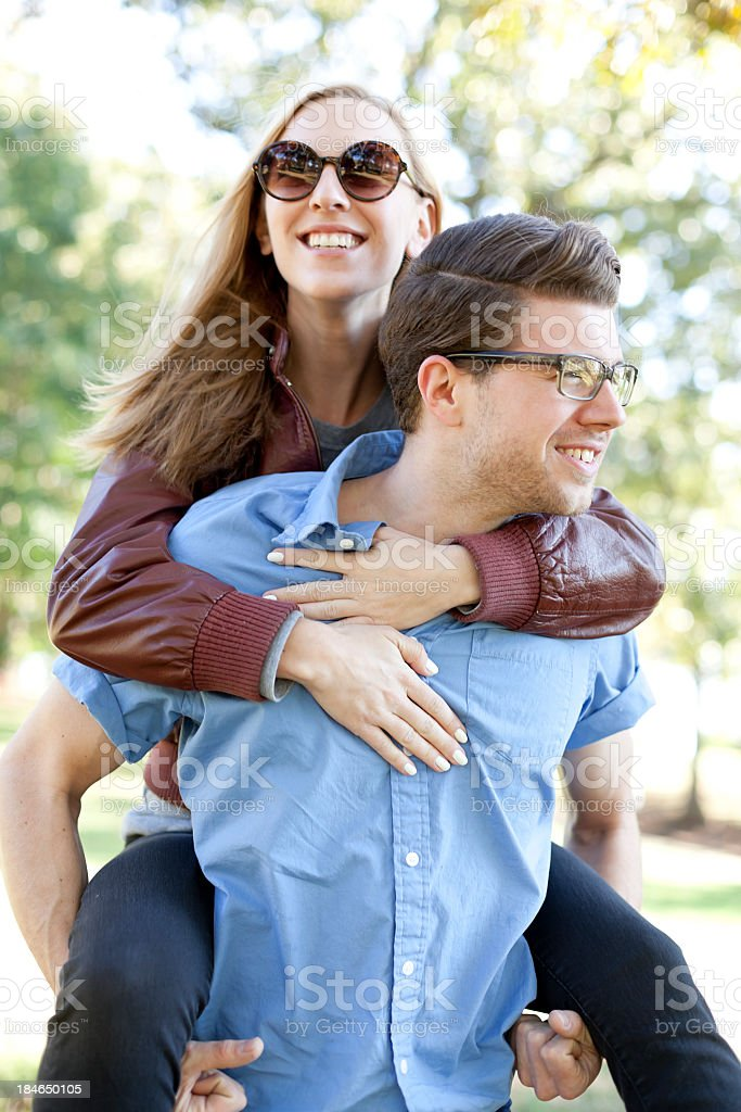 Young lady piggybacking on a man's back while both smile royalty-free stock photo