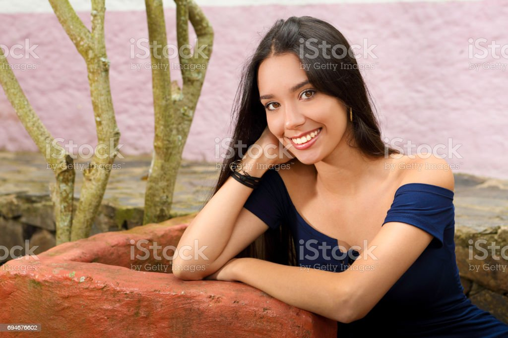 Young Lady Poses Sitting in a Garden stock photo