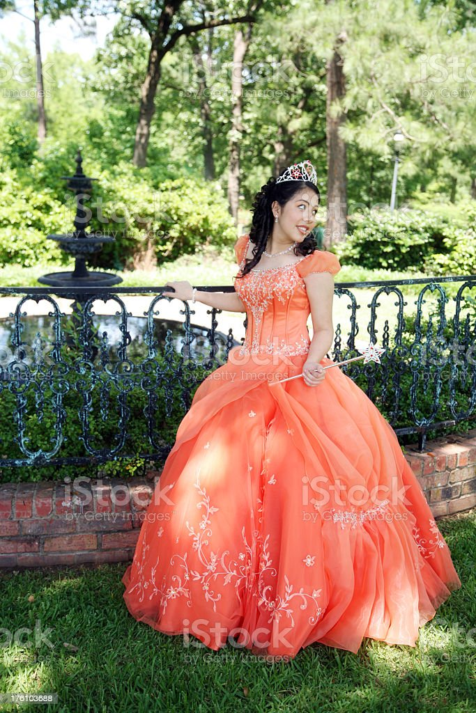 Young lady posing in an orange gown and a tiara stock photo