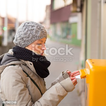 istock Young lady posting letters. 467961248