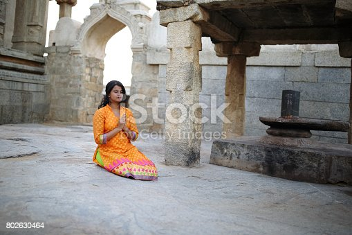 Young woman offering prayer sitting before the Shivalingam in the premises of an ancient temple at Lepakshi, Andhra Pradesh. The temple was built in 1538 CE and a popular tourist attraction in South India.