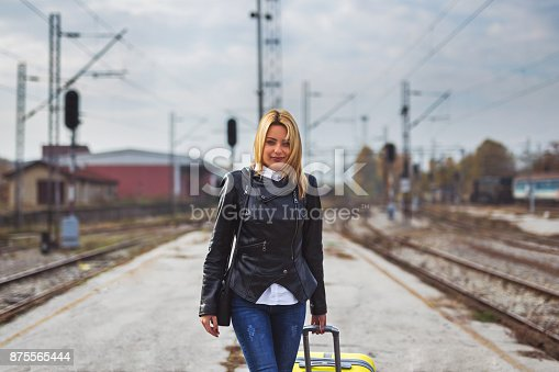 Young lady puling suitcase on old train station