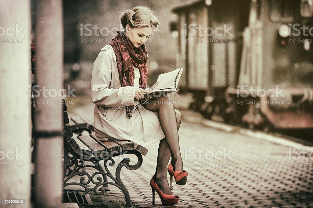 Junge Frau liest Buch, warten auf einen Zug – Foto