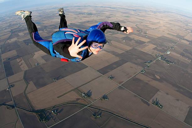 young lady skydiving whilst mid-air waving to camera - fallskärm bildbanksfoton och bilder