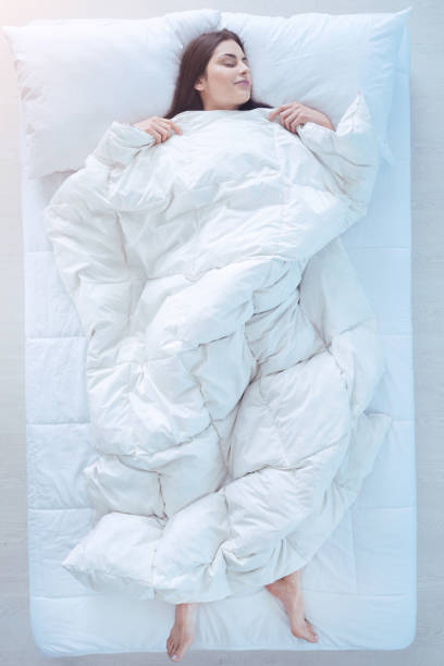 Young lady sleeping in bed with duvet over Comfortable sleep. Top view on a joyful brunette covered in a duvet falling asleep in a starfish position in bed. duvet stock pictures, royalty-free photos & images
