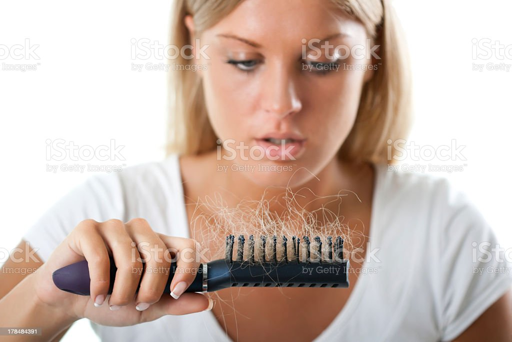 Young lady staring at a hairbrush with blond hair in stock photo