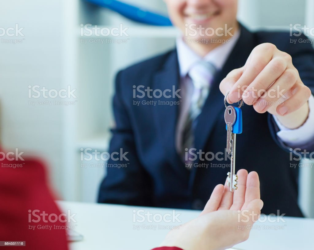 Young lady taking keys from male real estate agent during meeting after signing rental lease contract or sale purchase agreement. Independent woman purchasing new home, close up view stock photo