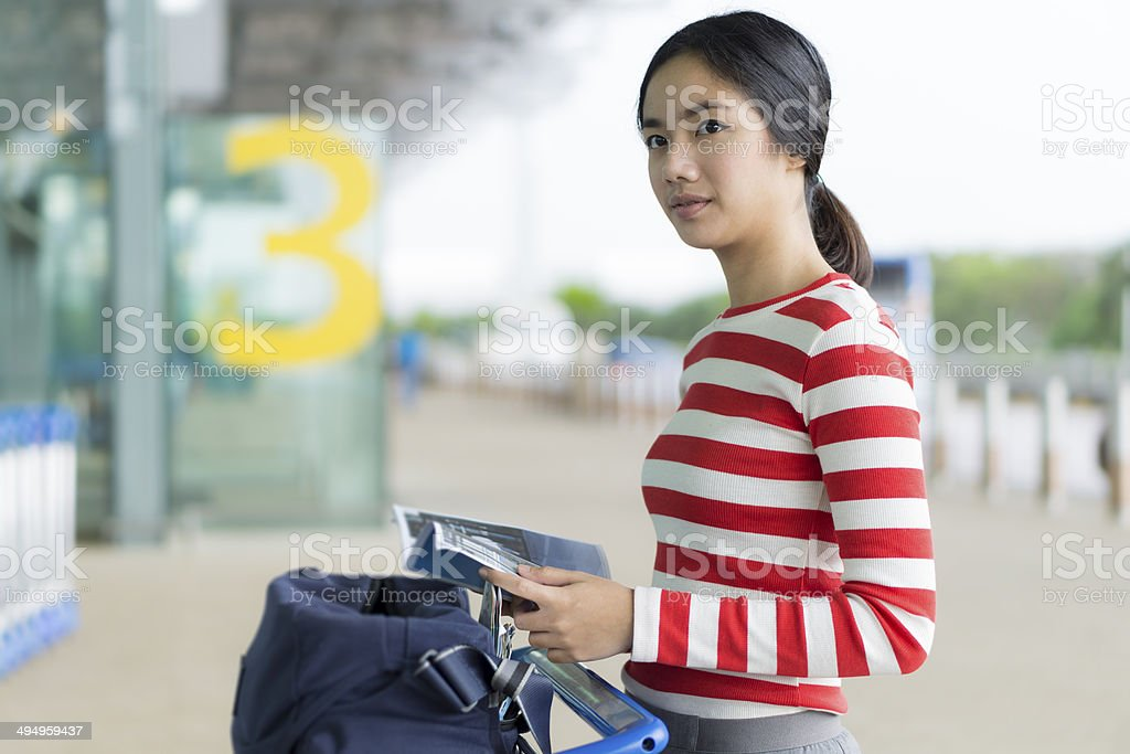Young lady traveller in red and white top in airport royalty-free stock photo