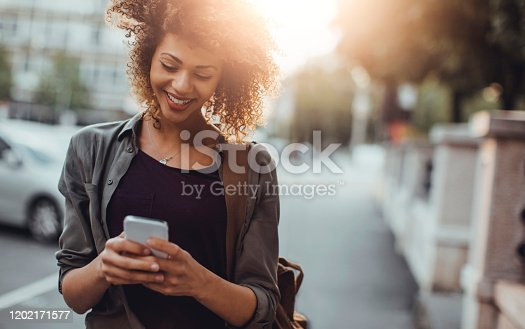 Close up of a young lady using a phone while on the street
