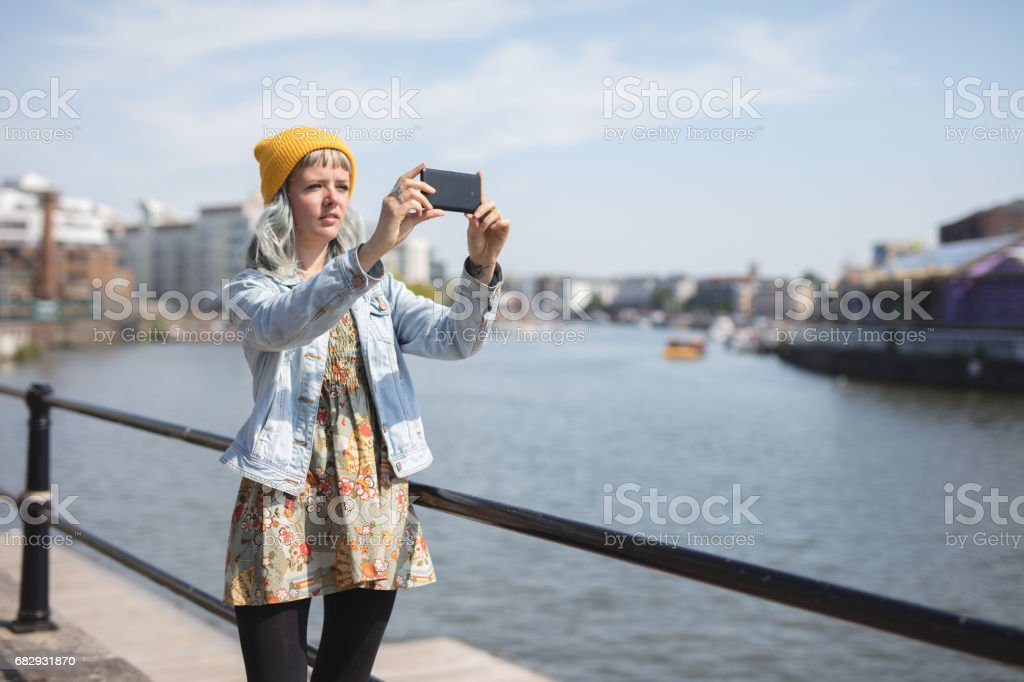 young lady using her phone by the waterfront royalty-free stock photo