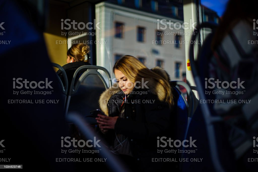 Young lady using mobile phone on public transport in Sweden stock photo