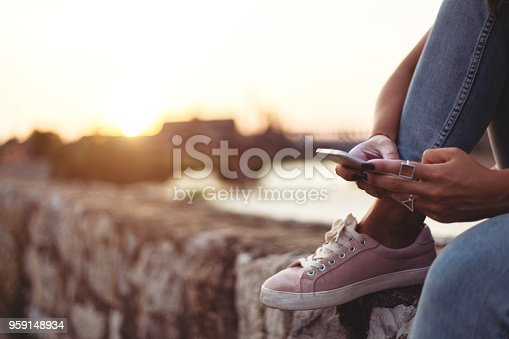 855341616istockphoto Young lady using smartphone near river 959148934