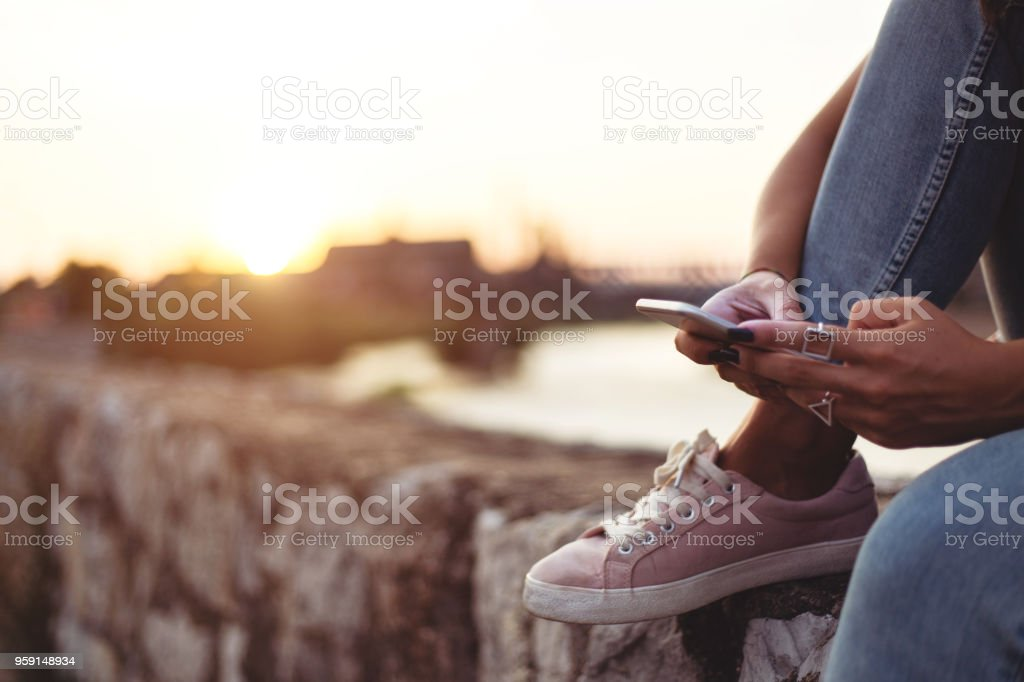 Young lady using smartphone near river stock photo