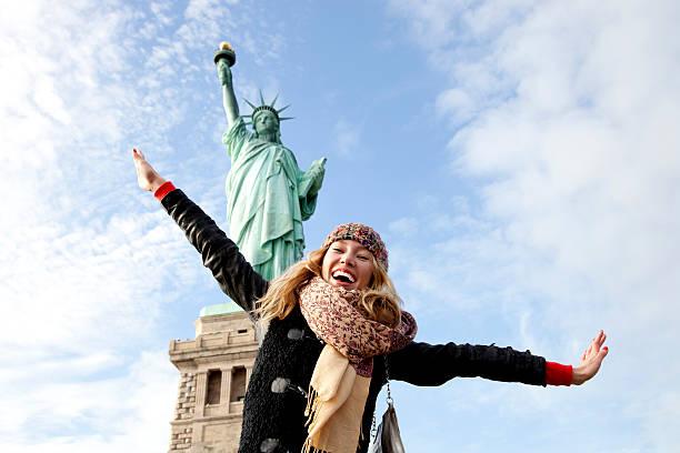 junge frau, die freiheitsstatue in new york - sightseeing in new york stock-fotos und bilder