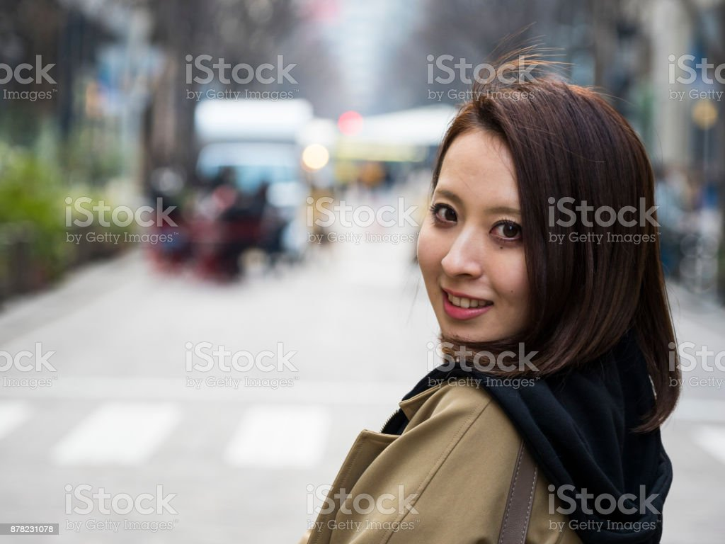 Young lady waiting for her friends on the street. stock photo