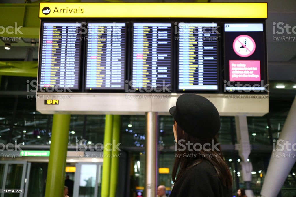 A young lady wearing a hat checking the arrival times in an airport terminal stock photo