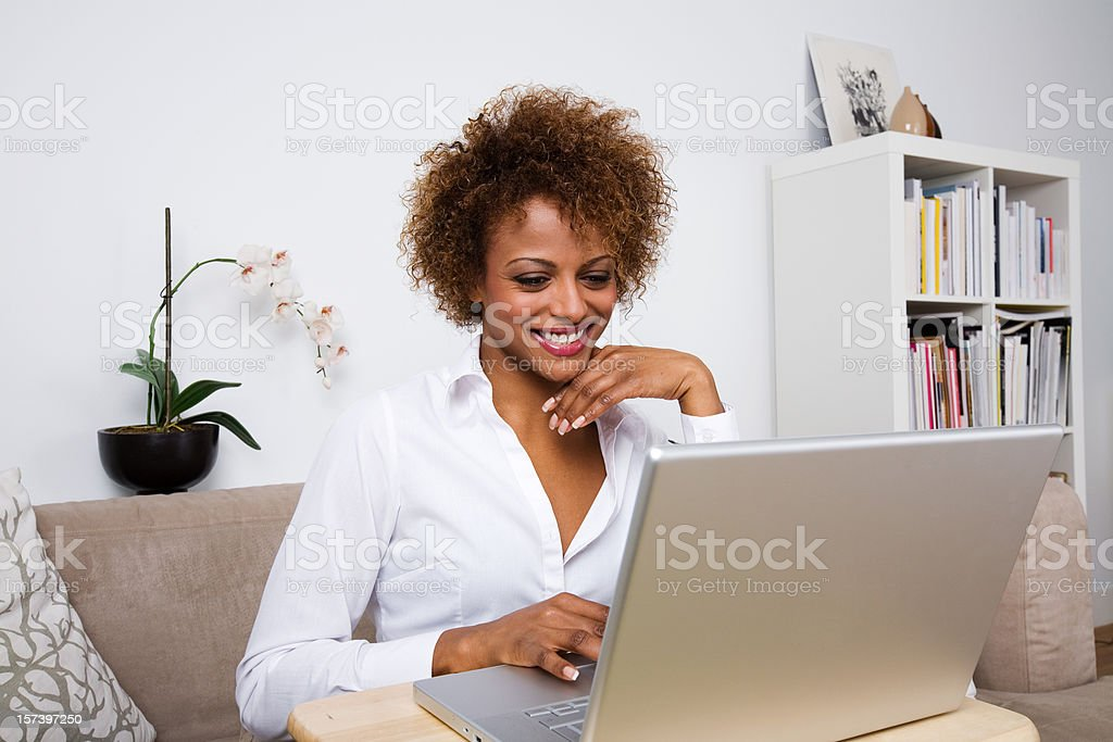 Young lady with laptop Young African lady sitting on a couch using a laptop. Adult Stock Photo
