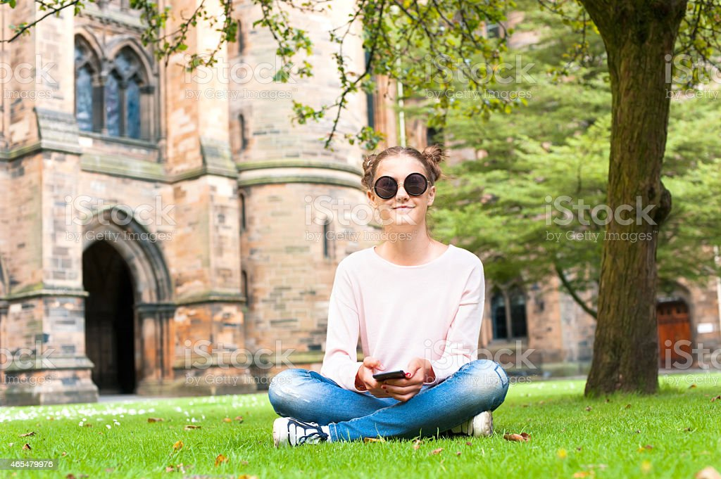 Young lady with mobile phone sitting in Glasgow University garden. stock photo
