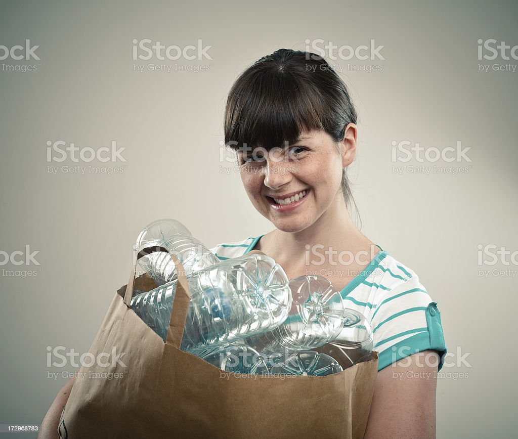 Young lady with plastic bottles in a paper bag royalty-free stock photo