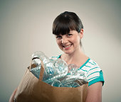 Young lady smiling while holding a paper bag full of empty plastic bottles.