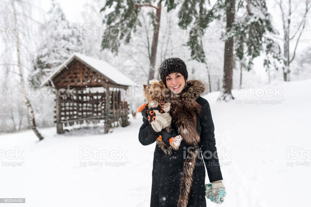 Young lady with small dog is on the snowy field. Tender feeling with a dog stock photo