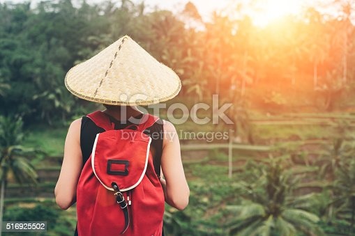 istock Young lady with traditional Asian hat and backpack 516925502