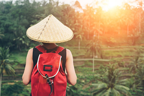 Young lady with traditional Asian hat and backpack stock photo