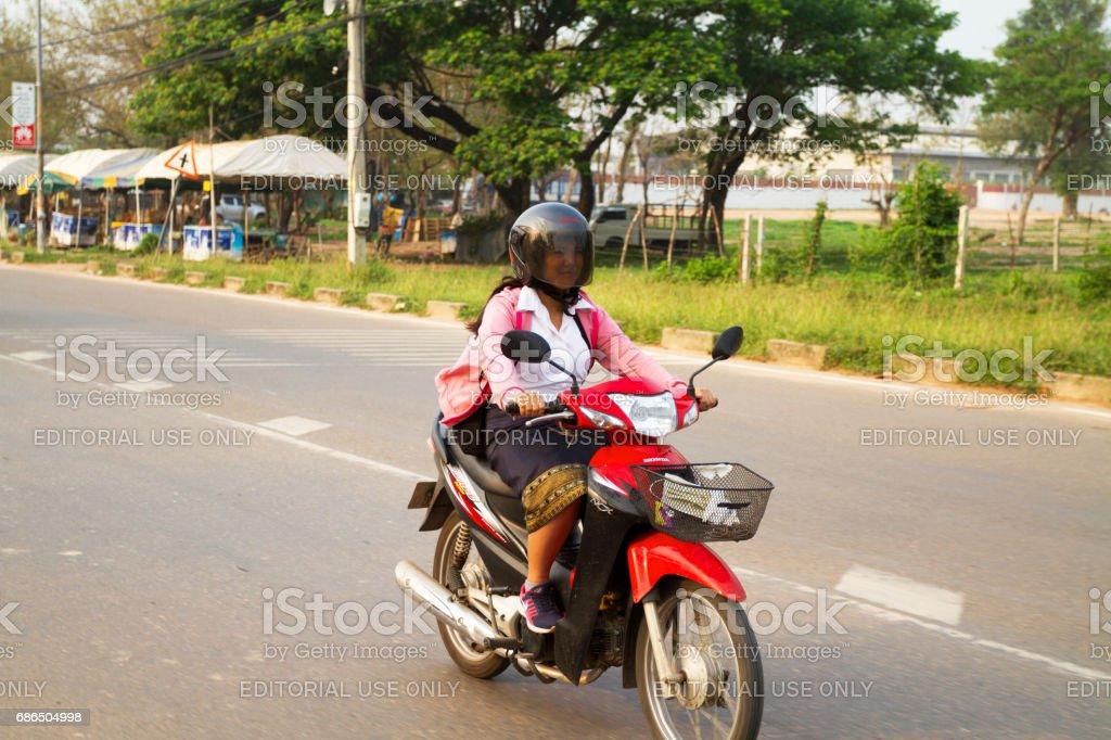 Laotiska kvinna på motorcykel i tidig morgon royaltyfri bildbanksbilder