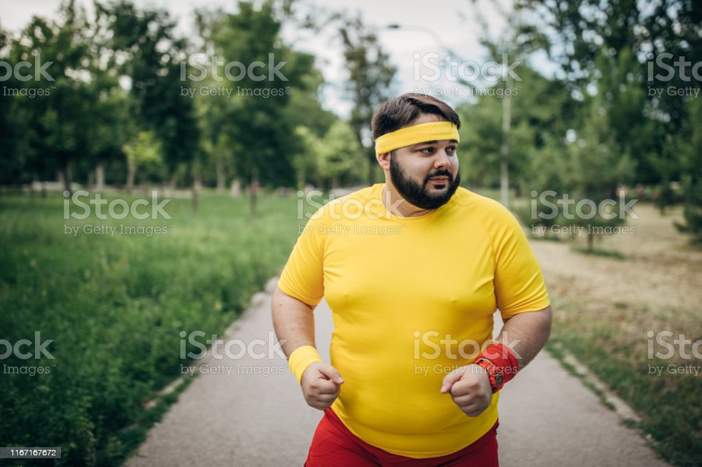 One man, young overweight man jogging alone in park.