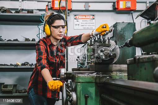 Portrait of hard working female industry technical worker or engineer woman confident serious face turner standing works on automatic universal cnc vertical milling machine for production of metal structures in an industrial manufacturing factory company. XXXL