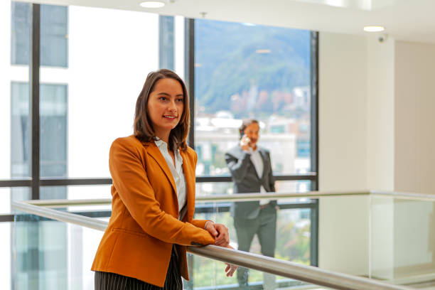 Young Latin American Lady Dressed In Business Casual Clothes Waits for A Colleague To Arrive In The Lobby Area On The Floor Of Her Office Building stock photo