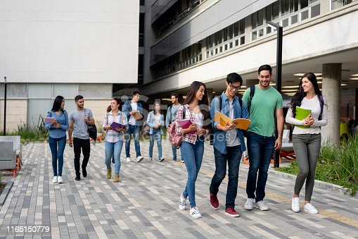 Young latin american students leaving the university campus after a day of class smiling