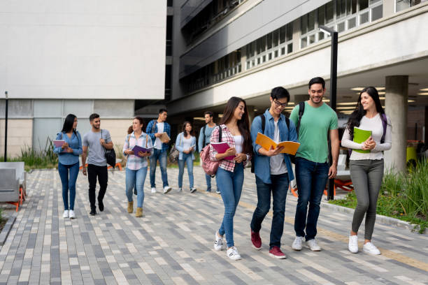 クラスの一日後に大学のキャンパスを去る若いラテンアメリカの学生 - 大学 ストックフォトと画像