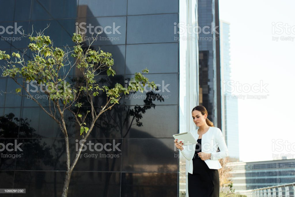 Young latin business executive reading from tablet stock photo
