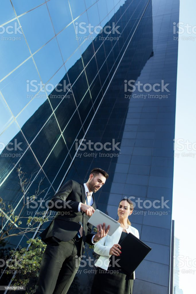 Young latin business executives reading from tablet outside stock photo