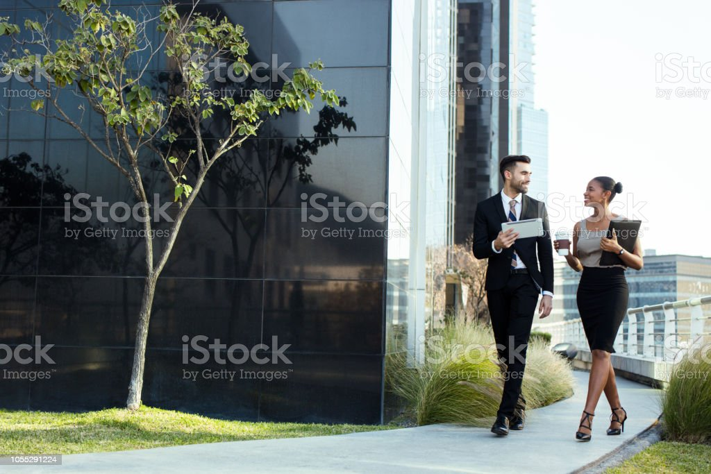 Young latin business executives walking and talking outside stock photo