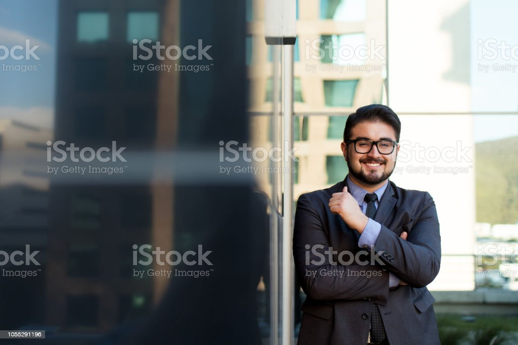 Young latin business man smiling and posing against a building stock photo