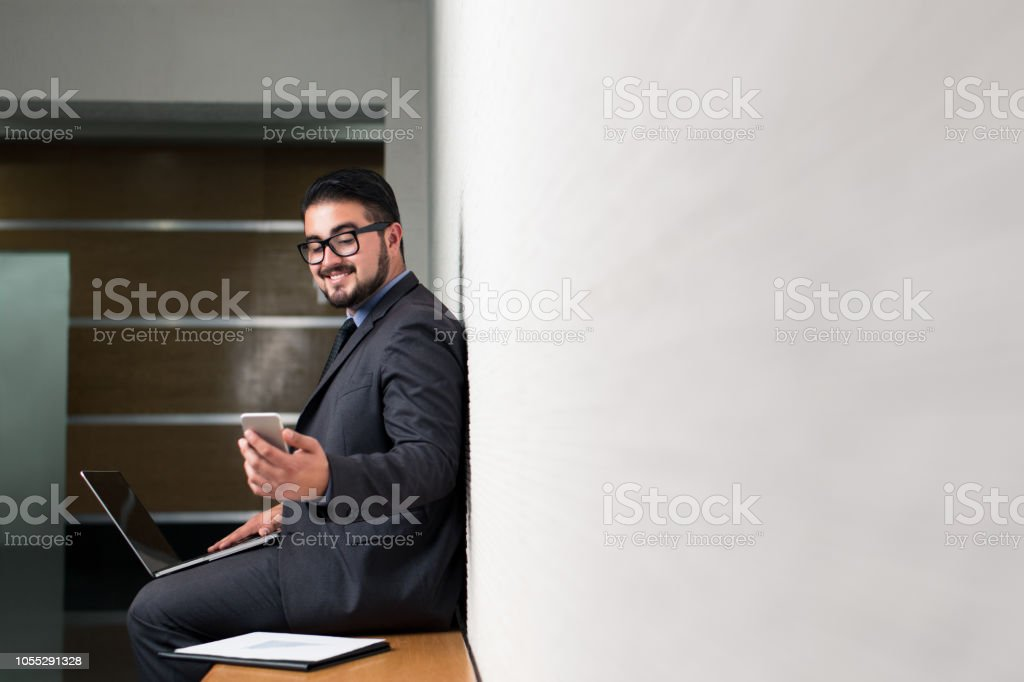 Young latin business man with laptop and phone in hand stock photo