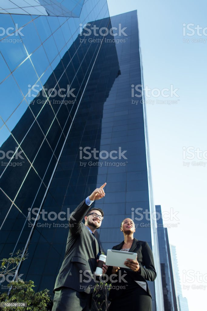 Young latin business partners with talking outside stock photo