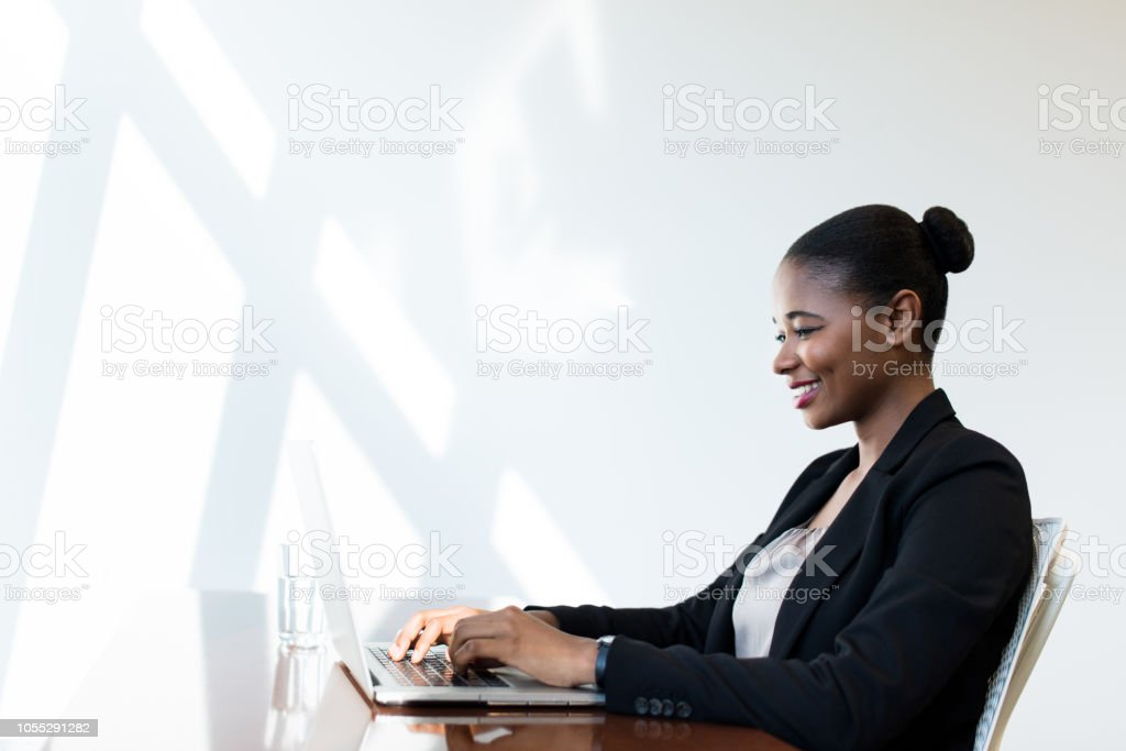 Young latin business woman working on laptop stock photo