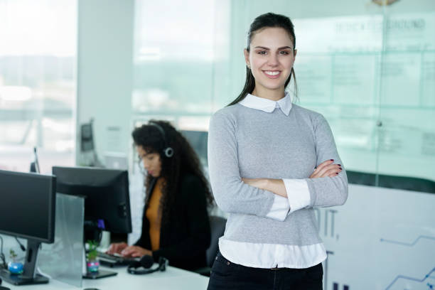 young latin businesswoman proud in the office young latino businesswoman of short hair between 22 to 32 years with glasses in the office of the call center happy for the results of the positives of the company, pointing to the camera 20 29 years stock pictures, royalty-free photos & images
