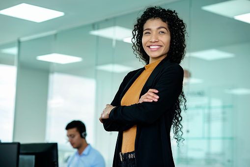young latino businesswoman of short hair between 22 to 32 years with glasses in the office of the call center happy for the results of the positives of the company, pointing to the camera