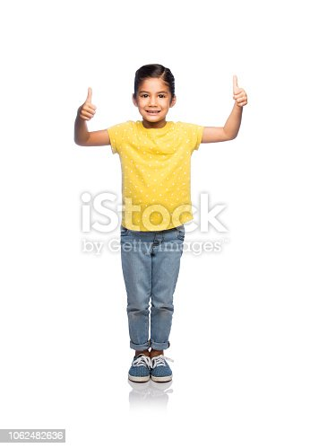 A very young little girl standing and giving two thumbs up against an isolated white background