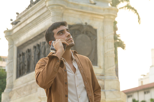 Young latin male portrait, traveling and talking by smartphone / cellphone using 5G Technology at Parque Seminario or Iguanas' Park, Guayaquil, Guayas, Ecuador, Latin America