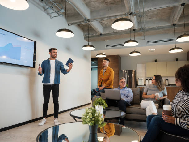 Young  latin man giving presentation in coworking space stock photo