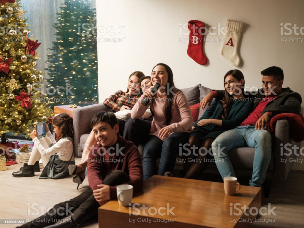 Young latin people sitting on sofa at home during christmas Young latin people sitting on sofa and watching tv together. 12-13 Years Stock Photo