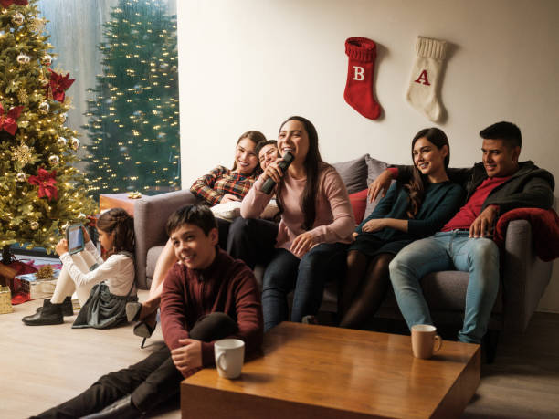 Young latin people sitting on sofa at home during christmas stock photo